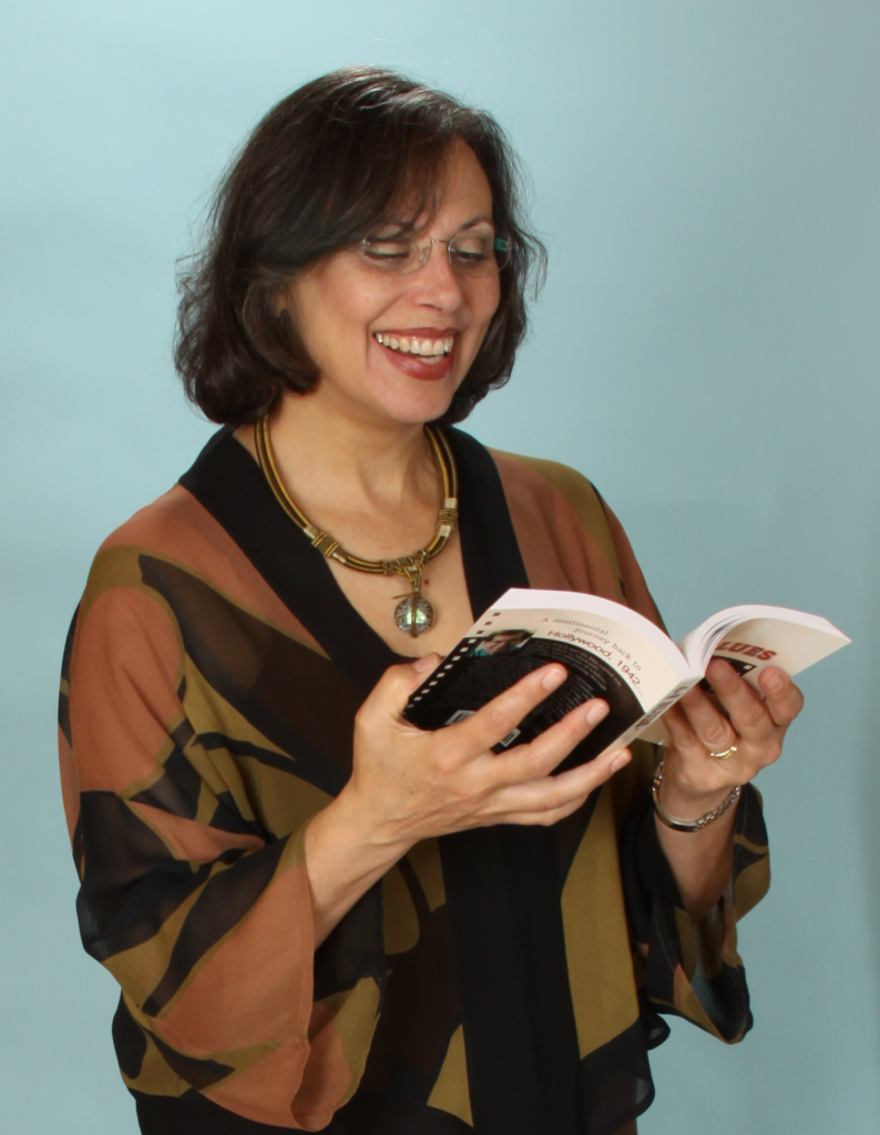 Judy Baker laughs while holding a book